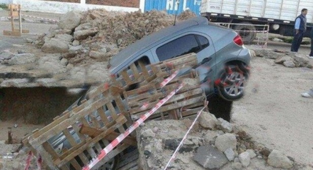 Por esquivar una moto cayó con su auto en un enorme cráter